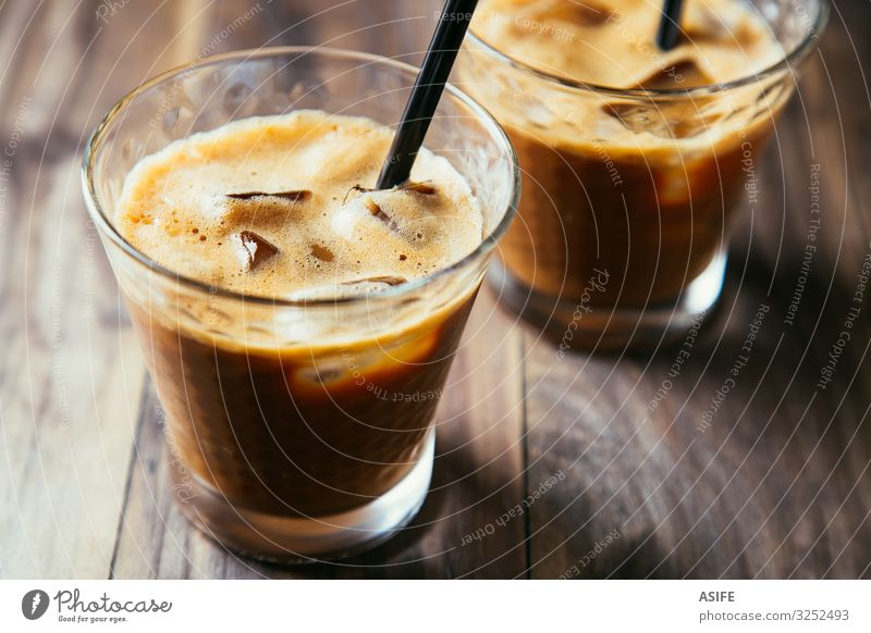 Gläser mit Eiskaffee-Latte Dessert Getränk Kaffee Sommer Tisch Restaurant Holz dunkel frisch lecker braun eisbedeckt melken Milchshake kalt Glas Eiswürfel Stroh