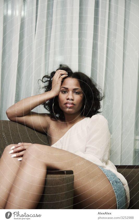 Junge Frau sitzt quer im Sessel Stil exotisch Freude schön Sinnesorgane Erholung Jugendliche Gesicht Beine 18-30 Jahre Erwachsene Top Hotpants schwarzhaarig
