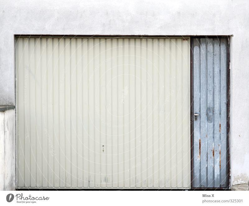 Garage Wohnung trist grau weiß Garagentor Tor geschlossen Farbfoto Gedeckte Farben Außenaufnahme Menschenleer Textfreiraum oben Textfreiraum Mitte