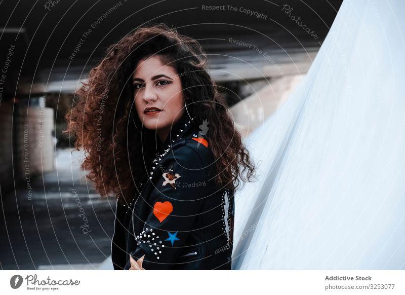 Junge Frau im Rocker-Outfit schaut in die Kamera Felsen Stil Jacke Leder schwarz streifen brünett Mode urban Großstadt lange Haare jung Straße gewelltes Haar
