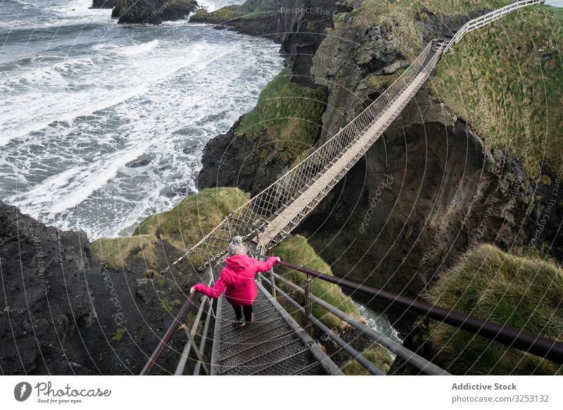 Frau überquert Seilbrücke zur Felseninsel Brücke MEER Insel Spaziergang Meer Nordirland durchkreuzen Küste carric a red Ufer Wasser Landschaft Selbstvertrauen