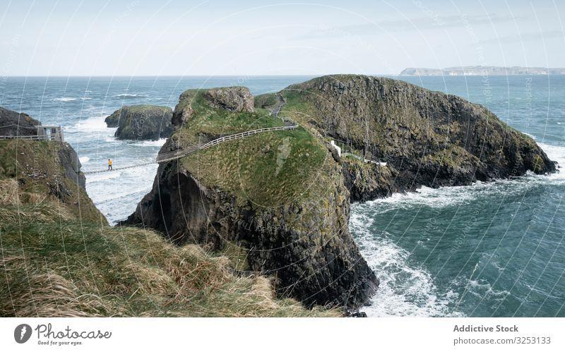 Touristen wandern auf einer Seilbrücke zwischen den Klippen in Nordirland Brücke Felsen MEER Spaziergang Meer Person durchkreuzen Küste Ufer Wasser Landschaft