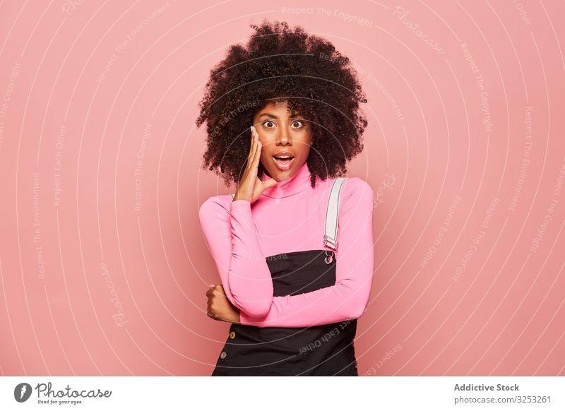 Geschockte afroamerikanische Frau schaut in die Kamera überrascht erstaunt schockiert jung lässig rosa Afroamerikaner schwarz stehen ethnisch Rollkragenpulli