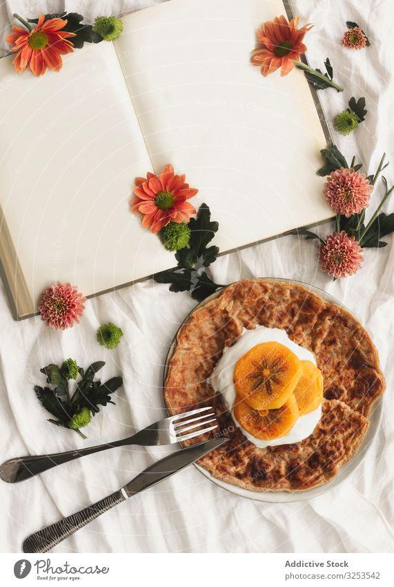 Crêpes mit Sahne und Kakipflaume Frucht Persimone Lebensmittel rötlich Dessert geschmackvoll Gabel Portion Messer Buch Blumen Scheibe lecker Teller Stoff
