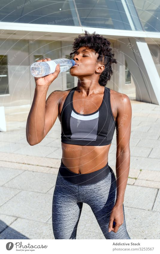 Glückliche afroamerikanische Sportlerin mit einer Flasche Wasser Großstadt Lächeln Frau sportlich trinken Pause ruhen frisch Erfrischung Erholung Konstruktion