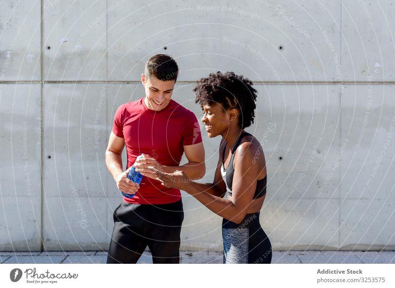Mehrrassiges sportliches Paar, das eine Pause macht und ein Smartphone benutzt Sportler benutzend Telefon Großstadt Zusammensein ruhen Glück teilen Lächeln