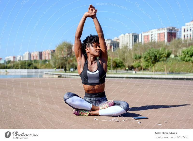 Afroamerikanische sportliche Frau, die in Lotus-Pose sitzt und die Hände nach oben streckt Lotussitz strecken Sportlerin Großstadt ruhen Erholung üben Yoga Zen