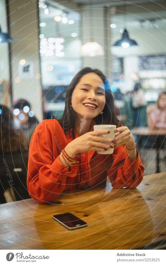Frau bei einer Tasse Kaffee Café trinken Smartphone benutzend Lächeln modern Browsen Gerät Apparatur soziale Netzwerke Surfen zuschauend erfreut Glück heiter