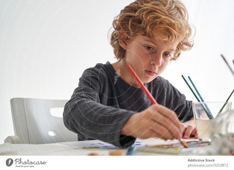Fröhlicher Junge malt zu Hause mit Aquarellfarben Lächeln Farbe Pinselblume heimwärts Kunst kreativ Bild Bildung Tisch sitzen Kind Werkzeug Handwerk lernen