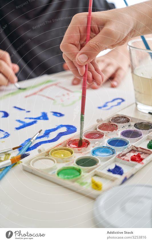 Kropfkitz-Malerei mit Aquarell auf Tisch Kind Farbe Wasserfarbe Pinselblume Papier heimwärts Kunst kreativ Bildung Inspiration farbenfroh Pigment Farbstoff