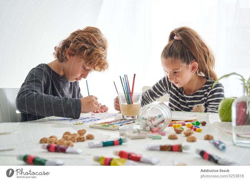 Fokussierte Kinder malen am Tisch Farbe Wasserfarbe Pinselblume fokussiert Freund heimwärts Kunst kreativ Bildung sitzen Zusammensein Mädchen Junge Pigment