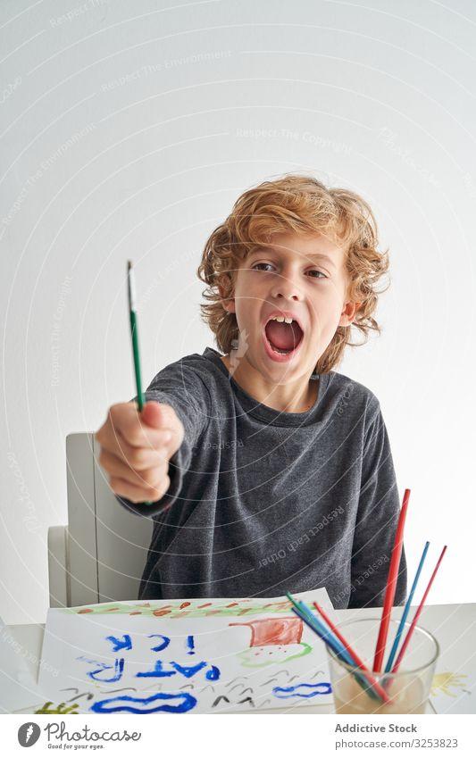 Aufgeregter Junge malt zu Hause Pinselblume aufgeregt schreien zeigen heimwärts Kunst kreativ Bild Wasserfarbe Bildung Tisch sitzen Kind Farbe Werkzeug Handwerk