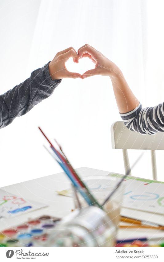 Kleine Künstler gestikulieren Herz und lächeln Kinder Farbe Pinselblume Glück Freund heimwärts Kunst kreativ Bildung Tisch sitzen Wasserfarbe Zusammensein