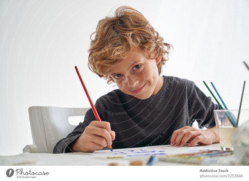 Fröhlicher Junge malt und schaut in die Kamera Lächeln Farbe Pinselblume heimwärts Kunst kreativ Bild Bildung Tisch sitzen Kind Werkzeug Handwerk lernen