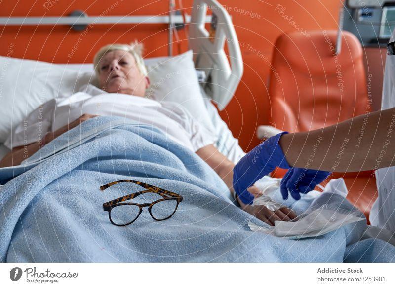 Pflanzenpflegerin injiziert Medikamente in den Arm eines reifen Patienten Krankenpfleger geduldig Einspritzung Medizin Station Krankenhaus Katheter älter