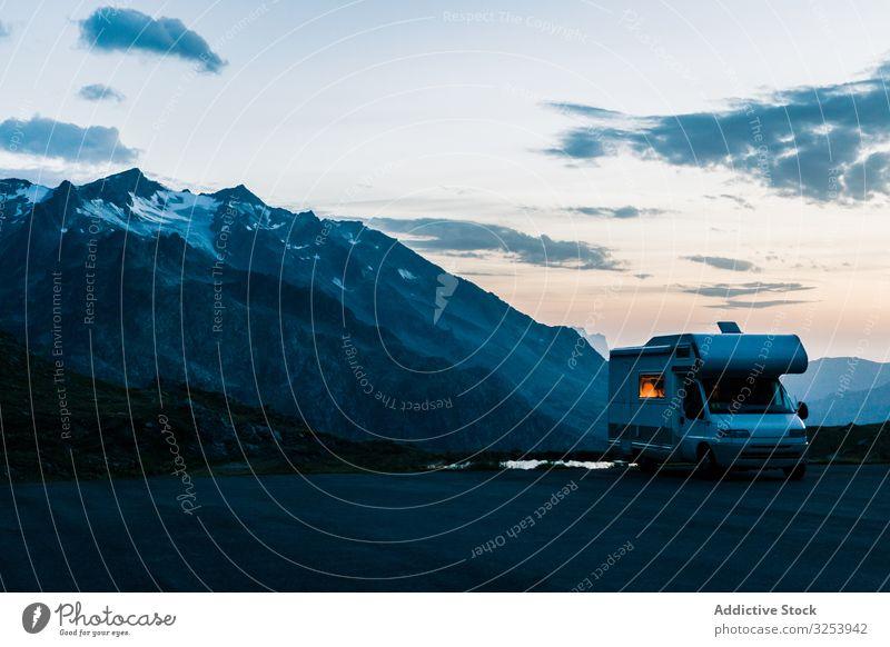 Wohnmobil auf der Straße entlang verschneiter Berge Berge u. Gebirge Urlaub Laufwerk Dämmerung Fahrzeug Ausflugsziel Natur Abenteuer Feiertag Autoreise Freiheit