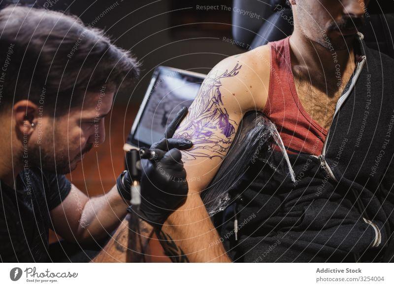 Meister tätowiert Unterarm eines männlichen Kunden Maschine Tattoo Skizze Gerät Werkzeug Instrument kreativ Kunst Pigment Nadel konzentriert fokussiert