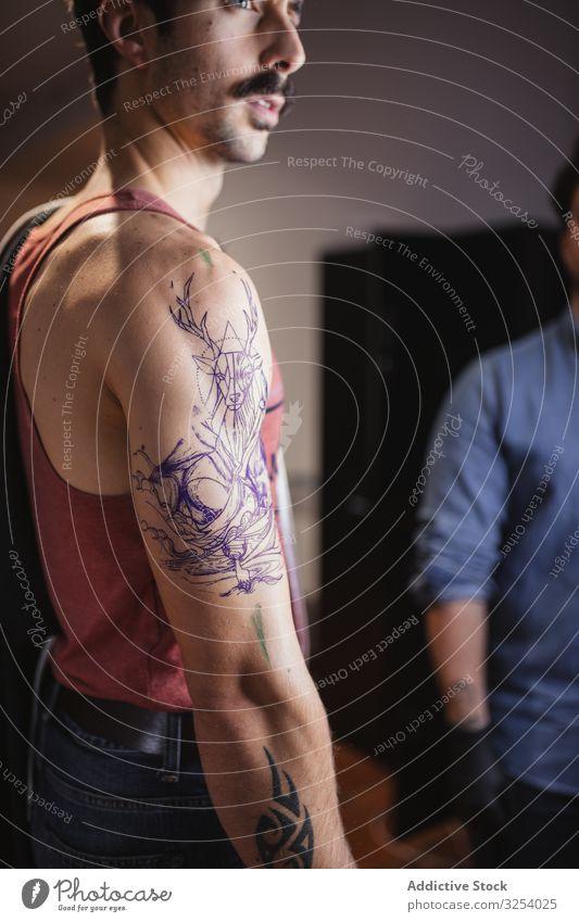Mann betrachtet Tätowierungsskizze auf dem Arm im Salon Tattoo Arme Aussehen Vorlage Zeichnung prüfen Skizze nachdenken Kunst vorsichtig ernst nachdenklich