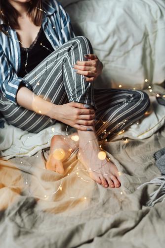 Frau sitzt in ihrem Bett mit weihnachtlichen Lichterketten. Abend gemütlich Feste & Feiern Feiertag gesichtslos Pyjama Weihnachten & Advent Hygge Unschärfe