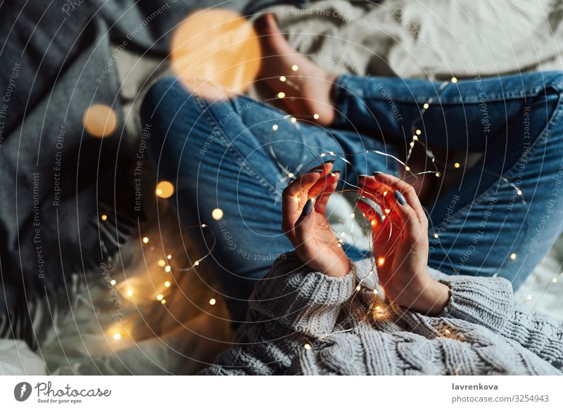 Frau sitzt in ihrem Bett mit weihnachtlichen Lichterketten. Bettwäsche Unschärfe Kaukasier Weihnachten & Advent bequem Jeansstoff gesichtslos Hand heimwärts