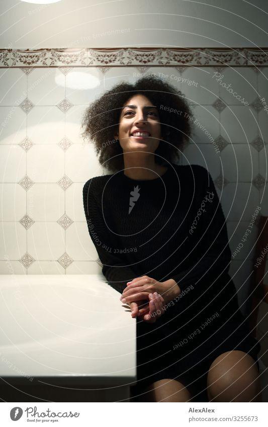 Junge Frau sitzt in Küche vor Fliesenwand Lifestyle Stil Freude schön Leben Fliesen u. Kacheln Muster Jugendliche Gesicht 18-30 Jahre Erwachsene Kleid
