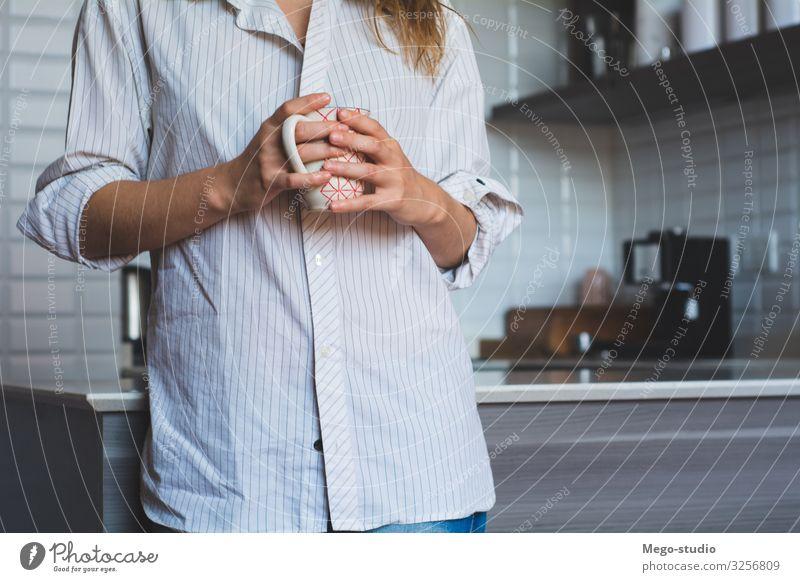 junge Frau, die zu Hause Kaffee trinkt Frühstück Getränk Tee Lifestyle Glück schön Gesicht Erholung Freizeit & Hobby Tisch Küche Mensch Erwachsene Wärme