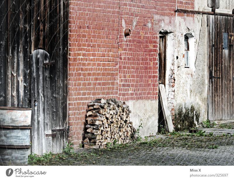 Holz vor der Hütte Häusliches Leben Wohnung Dorf Menschenleer alt Bauernhof Brennholz Holzstapel Scheune Scheunentor Backsteinwand Hof Farbfoto Außenaufnahme