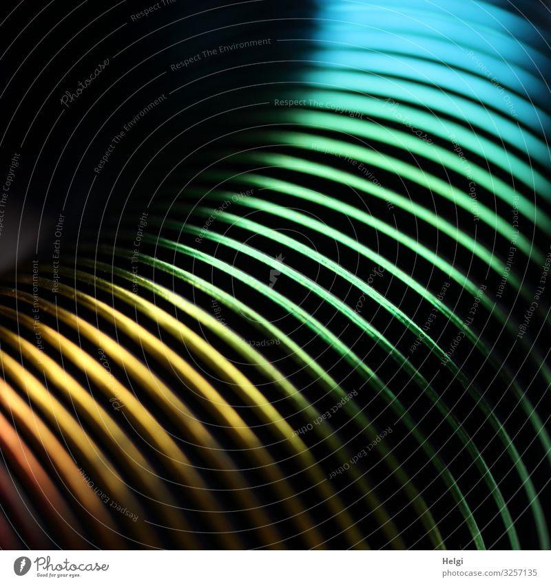 Nahaufnahme einer bunten Spirale aus Metall liegen außergewöhnlich glänzend einzigartig gelb grün türkis bizarr Zusammenhalt Farbfoto mehrfarbig Innenaufnahme