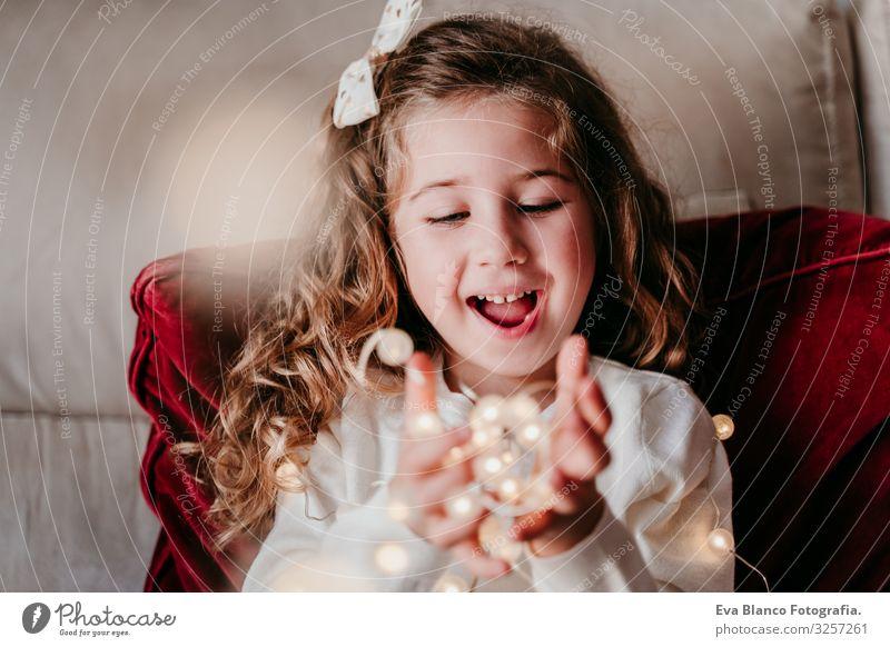 schönes Mädchen zu Hause, das mit einer Lichtergirlande spielt. Weihnachts-Konzept Weihnachten & Advent Girlande heimwärts blond blaue Augen Kind Liebe
