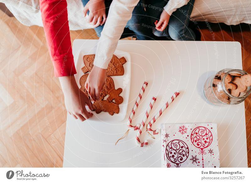 schönes Geschwisterpaar zu Hause bei einem leckeren Snack. Weihnachts-Konzept Plätzchen Süßwaren Hermano Schwester Weihnachten & Advent heimwärts blond