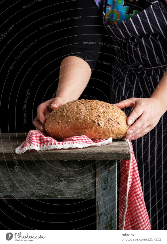 Frau hält in ihren Händen gebackenes Rundbrot Teigwaren Backwaren Brot Tisch Küche Mensch Erwachsene Hand Holz machen dunkel frisch braun schwarz weiß Tradition