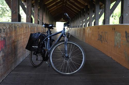 Fahrrad mit Gepäcktaschen in Holzbrücke Schönes Wetter Hütte Brücke Verkehr Personenverkehr Fahrradfahren Metall Ferien & Urlaub & Reisen blau braun grün Stadt