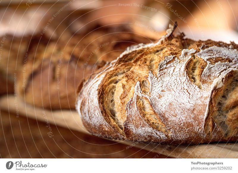 Sauerteigbrot mit knuspriger Kruste auf Holzregal. Bäckereiwaren Teigwaren Backwaren Brot Brötchen Ernährung kaufen Gesunde Ernährung Tradition Schwarzbrot