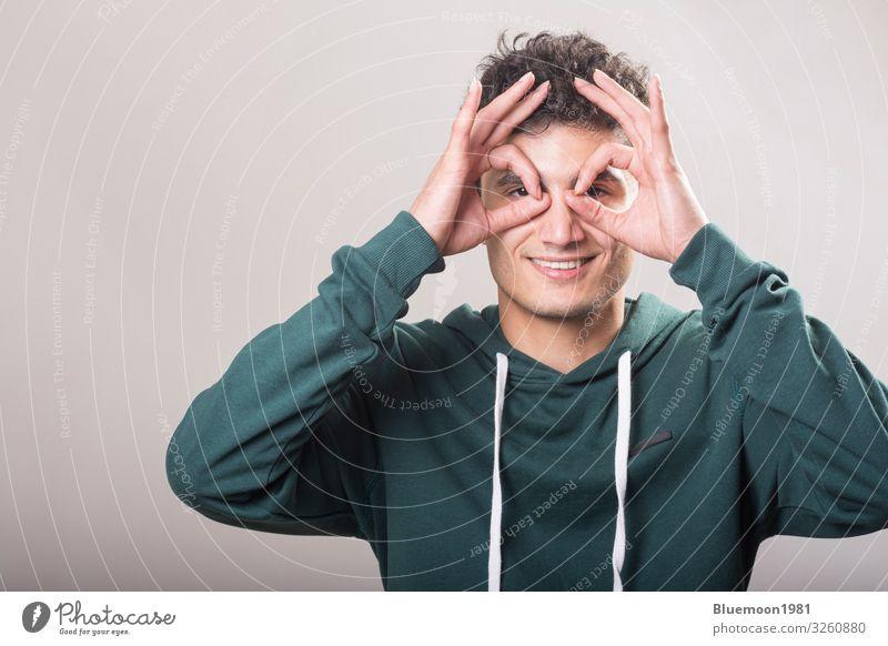 Junger Mann mit grünem Pullover und hält seine Hände Lifestyle Freude Glück Wellness Beruf Mensch Jugendliche Erwachsene Hand Finger 1 18-30 Jahre Mode Fernglas