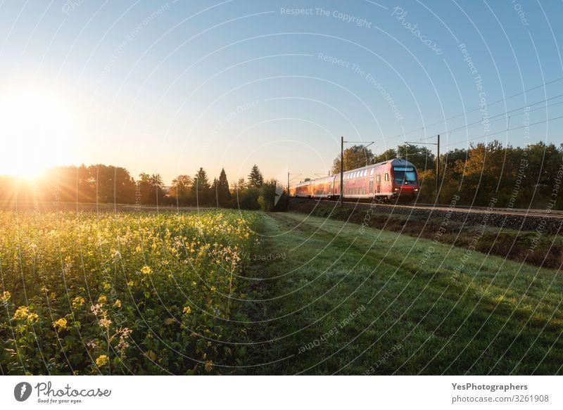 Roter Zug und Frühlingslandschaft bei Sonnenaufgang. Kontext der Frühjahrsreisen Ferien & Urlaub & Reisen Umwelt Natur Landschaft Sonnenuntergang Verkehr