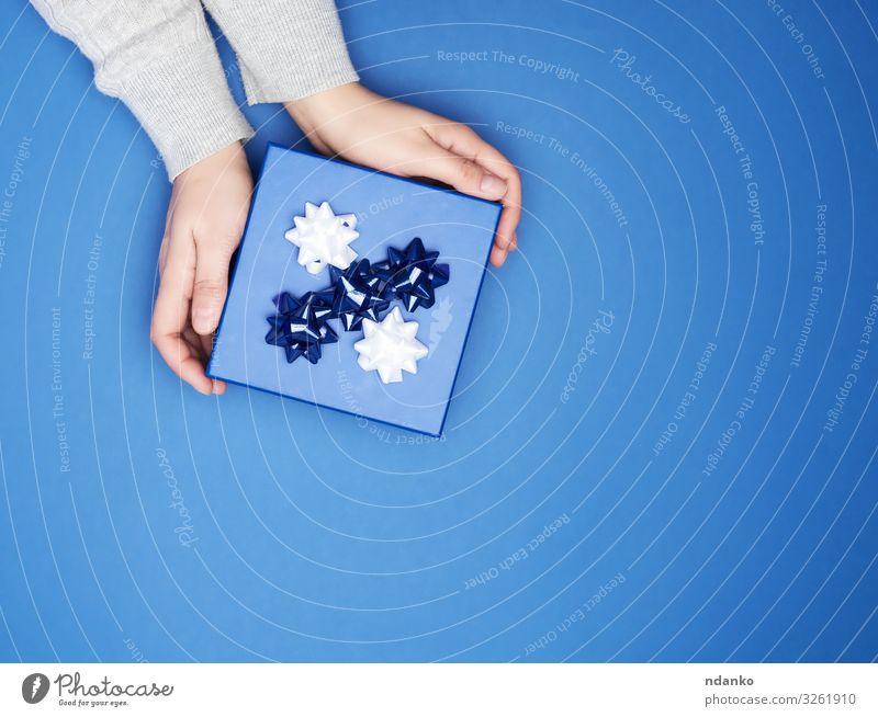 zwei Frauenhände halten geschlossenes quadratisches blaues Feld Dekoration & Verzierung Feste & Feiern Valentinstag Weihnachten & Advent Silvester u. Neujahr