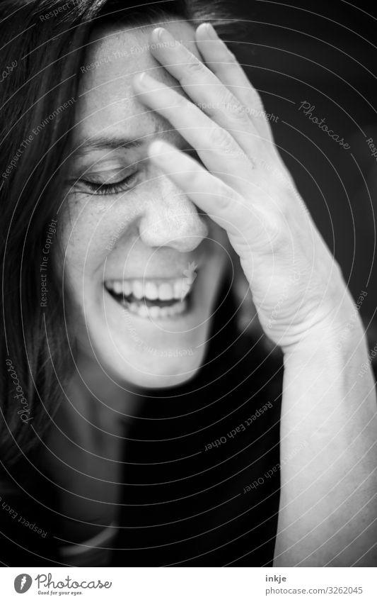 lachende Frau mit geschlossenen Augen und Hand an der Stirn Schwarzweißfoto Innenaufnahme Portrait Nahaufnahme Frauenportrait Lachen fröhlich amüsiert Geste