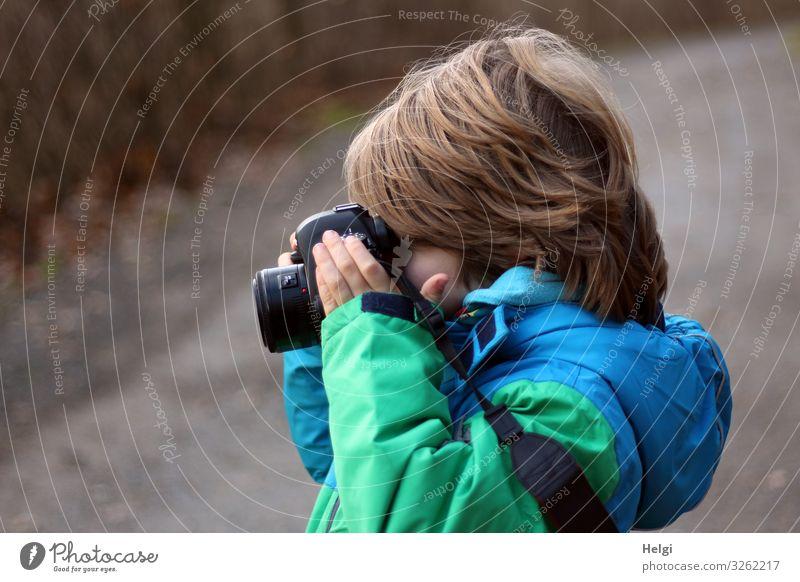 Profilaufnahme eines kleinen Jungen mit halblangen Haaren, der in eine Kamera schaut Fotokamera Mensch maskulin Kind Kindheit 1 3-8 Jahre Natur Winter