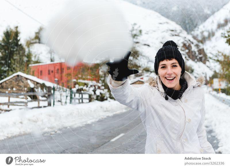 Lächelnde Frau spielt mit Schnee auf dem Land Schneeball Landschaft spielen Winter Freude Berge u. Gebirge ruhen Resort Feiertag Natur Dorf ländlich kalt Spaß