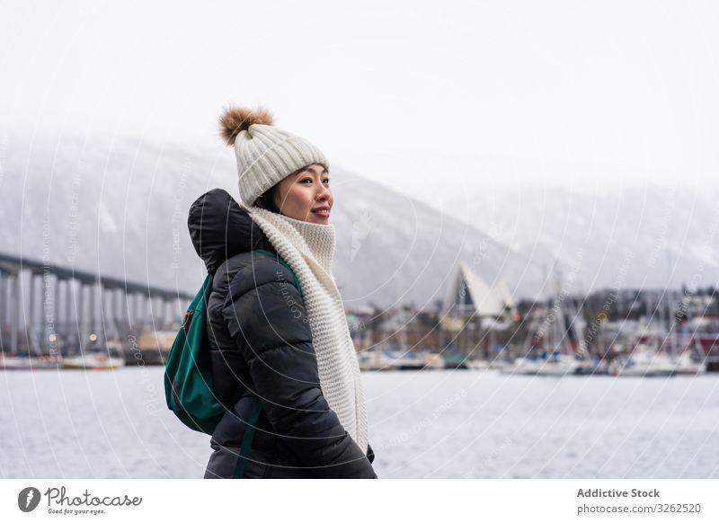 Asiatische Touristin in warmer Kleidung auf verschneitem Feld nahe der Stadt Tourismus laufen Winter Großstadt Frau Bekleidung reisen Schnee Gebäude Feiertag