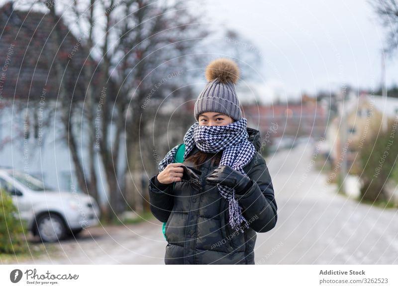 Erfreute asiatische Touristin in warmer Kleidung in verschneiter Natur reisen Winter Schnee Berge u. Gebirge Frau laufen Bekleidung Lächeln zufrieden Inhalt