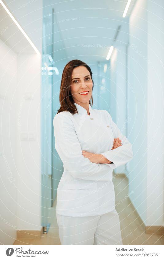 Selbstbewusster Zahnarzt in weißer Uniform mit verschränkten Armen, der in die Kamera schaut Arzt Lächeln selbstbewusst dental Klinik medizinisch Medizin