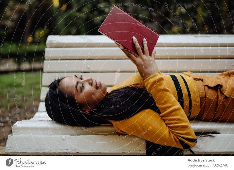 Anmutige langhaarige Asiatin liest Buch auf Parkbank Frau lesen stylisch Bank weiß Mode Model elegant asiatisch klug trendy Dame modisch brünett lernen