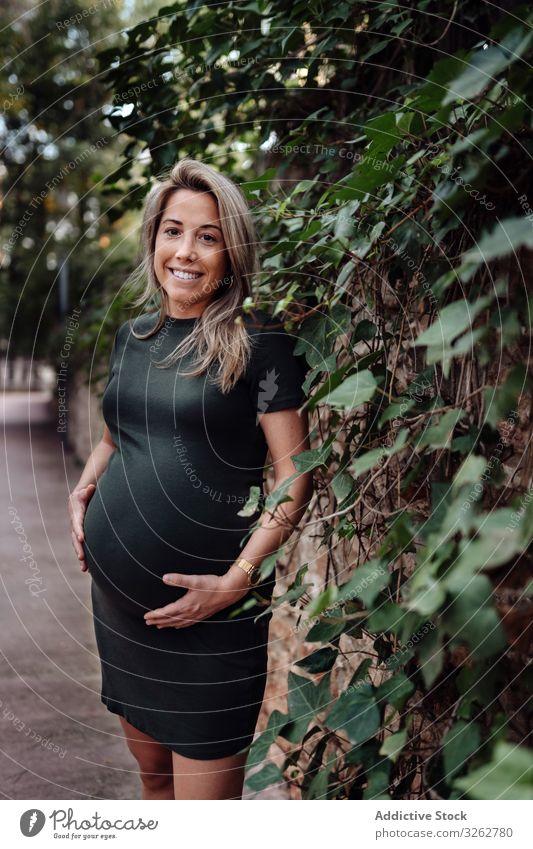 Charmante schwangere Frau steht auf einem Gehweg im Park Laufsteg Weg Sommer Glück Lächeln Kleid Natur grün Wald Bäume Holz Straße Mutter Fruchtbarkeit