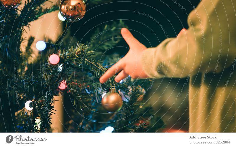 Junge schmückt Weihnachtsbaum am Abend Weihnachten Baum Dekor Feuerstelle Wohnzimmer hängen Kugel traditionell heimwärts Feier Kind wenig fröhlich Feiertag