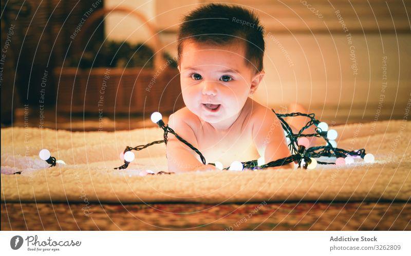 Baby spielt mit Lichtergirlande am Weihnachtstag spielen Weihnachten Girlande farbenfroh gemütlich Abend Vorabend Teppich Stock niedlich bezaubernd Kind Glück