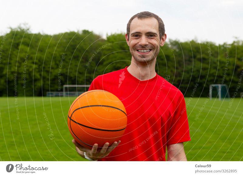 Junger Mann mit Basketball Lifestyle Sommer Sport Mensch Park Fitness spieler basketballspieler draussen sportplatz training mann sportlich lachen freundlich