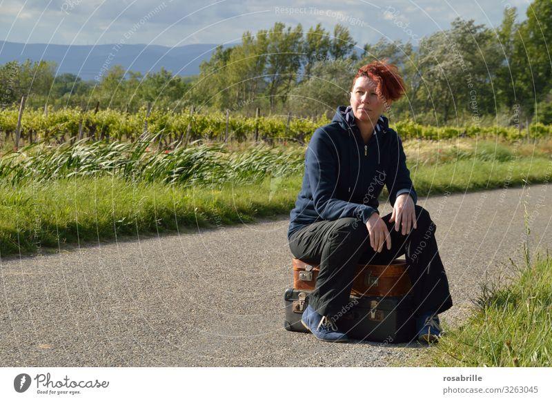 Frau mittleren Alters sitzt abwartend auf gepackten Koffern auf einer schmalen Landstraße im Grünen bei Wind Ferien & Urlaub & Reisen Erwachsene 1 Mensch