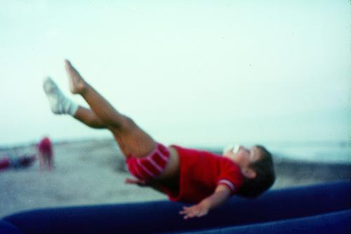 Kleines Mädchen mit Schnuller, fliegt, springt auf einer Luftmatratze am Strand vom Meer in die Luft. Freude Fitness Sinnesorgane Spielen