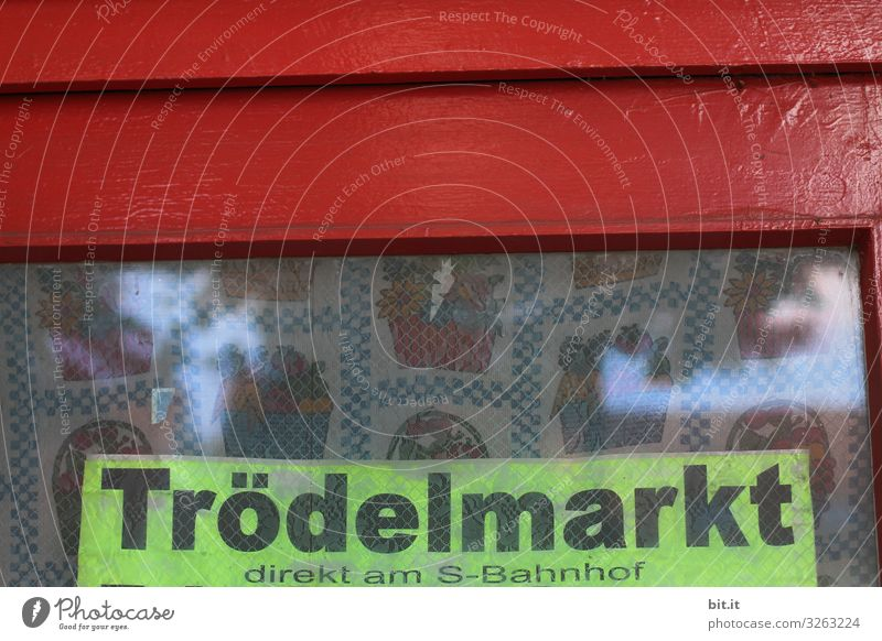 Schwarzer, dicker Schriftzug: Trödelmarkt, geschrieben auf Schild in Neon, hängt in altem Fenster, mit rotem Rahmen und nostalgischen Vorhang, hinter der Scheibe, als Werbung, Hinweis, Ankündigung, Programm für einen Flohmarkt am S-Bahnhof in der Stadt.